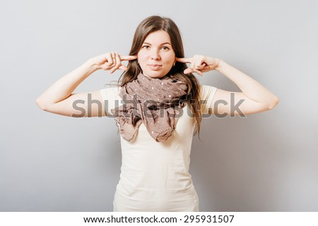Young woman covering her ears with her hands. On a gray background. - stock photo