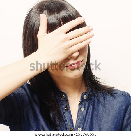 Young woman covering her eyes - stock photo