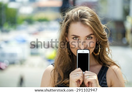 Young woman covers her face screen smartphone on a background summer street - stock photo