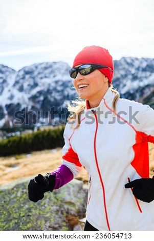 Young woman cross country trail running in mountains on winter fall sunny day. Female beautiful blonde runner training exercising outdoors, fitness in nature, sunset. - stock photo