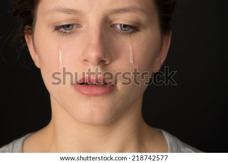 Young woman crying on a black background. - stock photo