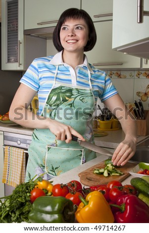 Young woman cutting vegetables in a kitchen.  Pretty girl in is cooking in the kitchen. home life: woman preparing something to eat. Smiling female standing and cutting cucumber in the kitchen. - stock photo