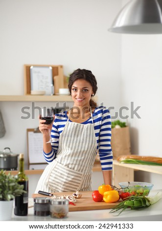 Young woman cutting vegetables in kitchen, holding a glass of wine - stock photo