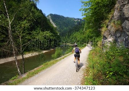 Young woman cycling along Dunajec river - Poland - stock photo