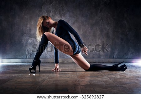 Young woman dancer in black clothing on wall background. - stock photo