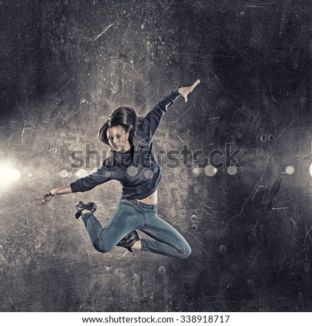 Young woman dancer jumping in spotlights on dark background - stock photo
