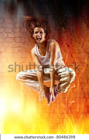 Young woman dancer jumping. With fire effect. - stock photo