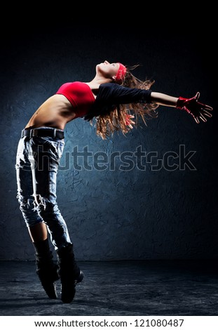 Young woman dancer. On wall background. - stock photo