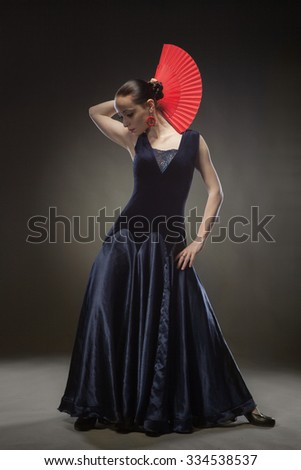 young woman dancing flamenco in blue dress on black background - stock photo