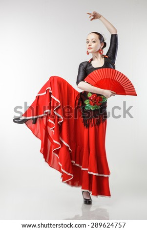 young woman dancing flamenco in red dress with fan isolated on white background - stock photo