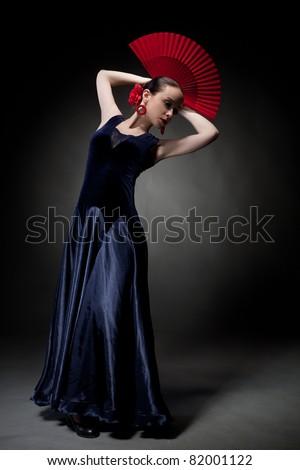 young woman dancing flamenco on black - stock photo
