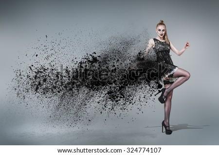 Young woman dancing inside cloud of dust - stock photo