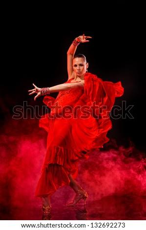 Young woman dancing Latino on dark smoky background. - stock photo