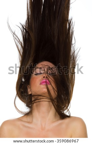 Young woman dancing with her long hair fluttering in motion, isolated on white - stock photo