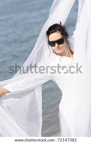 Young woman 30-35 dancing with white scarf moving by wind - stock photo