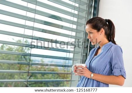 Young woman day dreaming looking window blinds drinking tea - stock photo