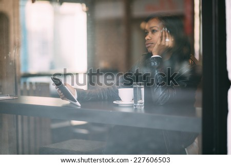 Young woman daydreaming in coffee shop - stock photo