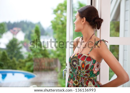 Young woman daydreaming while standing near door - stock photo