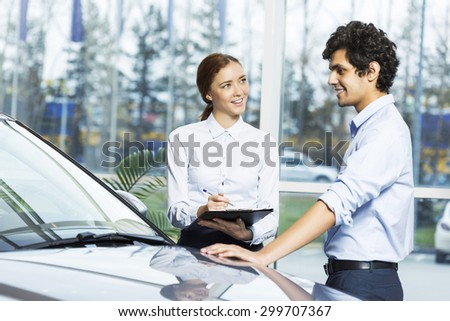 Young woman dealer in auto salon presenting car to customer - stock photo