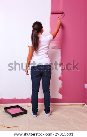 Young woman decorating the wall in her new home. - stock photo