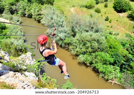 young woman descending on a zip-line (flying fox) - stock photo