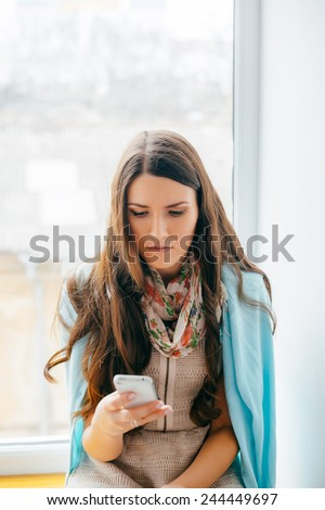 Young woman dials number on mobile phone - stock photo