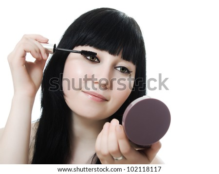 young woman directs a make-up eyelash on a white background. - stock photo