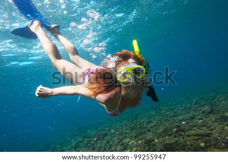 Young woman diving on a breath hold and making bubbles over coral reef in blue transparent sea - stock photo