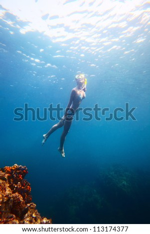 Young woman diving on a breath hold in a tropical sea - stock photo
