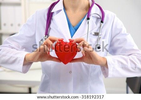 Young woman doctor holding a red heart, in office - stock photo