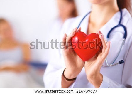 Young woman doctor holding a red heart, isolated on white backg - stock photo
