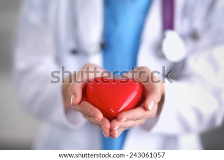Young woman doctor holding a red heart, standing on gray - stock photo
