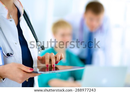 Young woman  doctor holding a tablet pc - stock photo