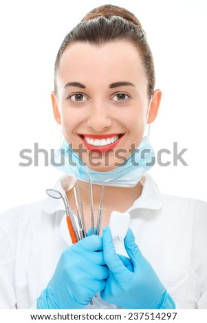 Young woman doctor holding dental equipment and looking at camera on white background - stock photo