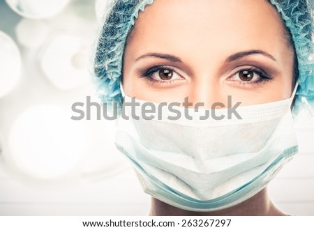 Young woman doctor in cap and face mask in surgery room interior - stock photo
