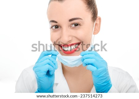 Young woman doctor taking off operation mask smiling and looking at camera on white background - stock photo
