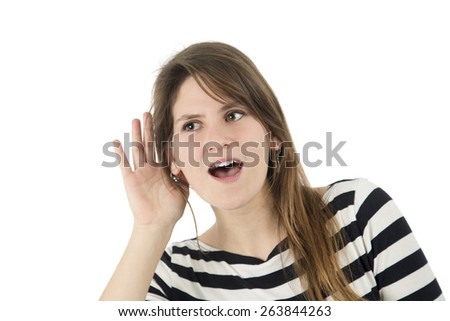 Young woman doing a hearing gesture against a white background - stock photo