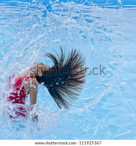 young woman doing a spin with her hair in the pool - stock photo