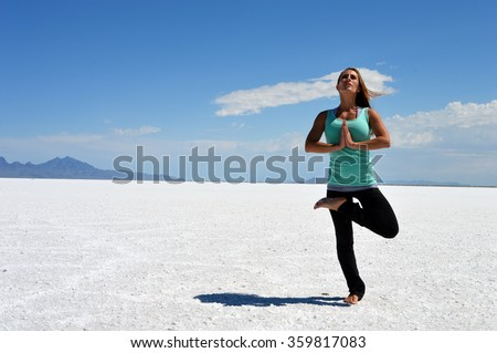 Young woman doing a yoga tree pose at the Bonneville Salt Flats in Utah. - stock photo