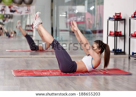 Young woman doing abs workout in a gym on a mat - stock photo