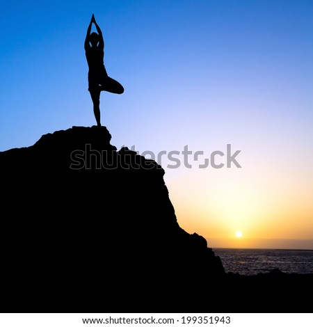 Young woman doing beautiful yoga pose tree, sunset silhouette in mountains over blue sky and clouds with sun sunlight background. Healthy lifestyle successful fitness exercise concept. - stock photo