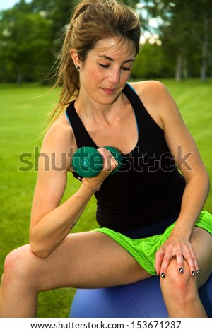 Young woman doing bicep curls on an exercise ball, in a park. - stock photo