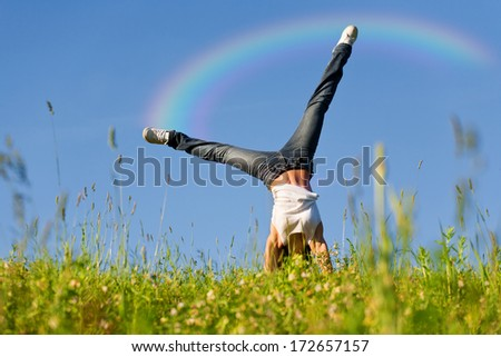 Young woman doing cartwheel on grass during beautiful spring day.Rainbow digitally added. - stock photo