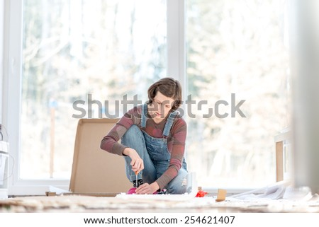 Young woman doing DIY repairs at home putting together self assembly furniture using a screwdriver. - stock photo