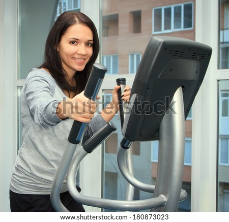 young woman doing exercise on a elliptical trainer - stock photo
