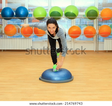 Young woman doing exercise on bosu ball - stock photo