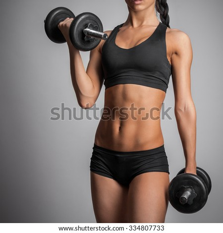 young woman doing exercise with dumbbell - stock photo