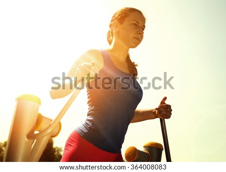 Young woman doing exercises on elliptical trainer.Woman looking away while exercising.Horizontal shot. - stock photo