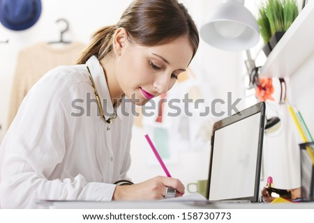 Young woman doing fashion sketches. / Fashion woman blogger working in a creative workspace.  - stock photo