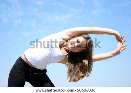 Young woman doing fitness exercises against blue sky - stock photo